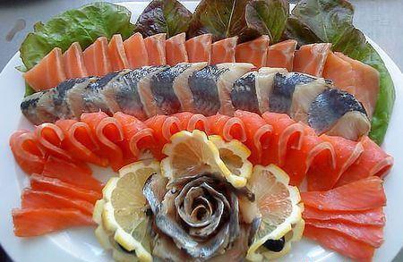 рыбная нарезка с листьями салата и лимоном