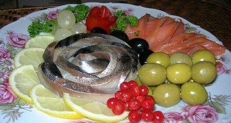 рыбная нарезка, украшенная оливками, лимоном и клюквой