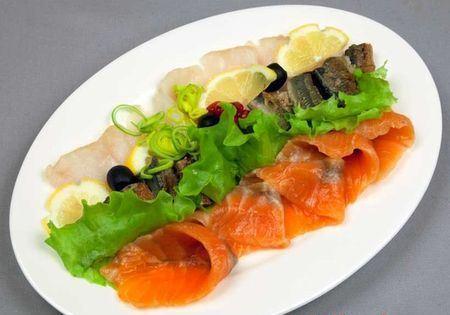 рыбная нарезка с зеленью салата и лимоном