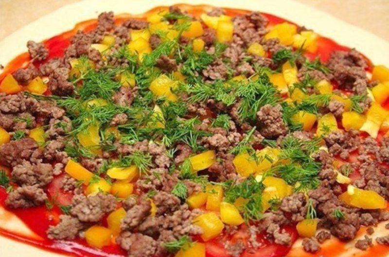 На лепешку выложить фарш, помидоры, перец и зелень